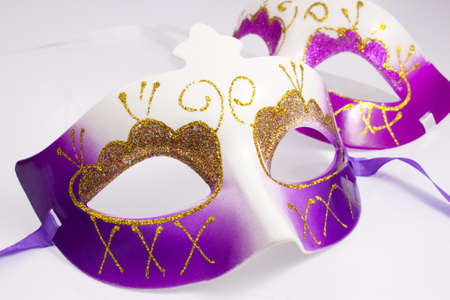 Purple and pink carnival masks on a white background photo