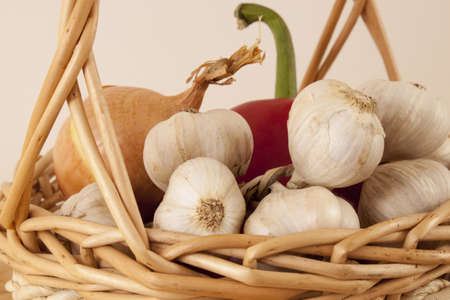 Garlic, onion and red pepper in wicker basket Stock Photo - 12597423