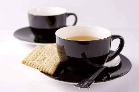 A cup of green tea and biscuit on a white background photo