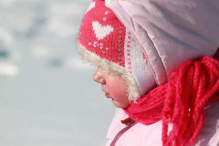Girl playing in the snow A child in a pink hat in winter Stock Photo - 13561906