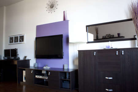 Living room with a purple wall of TV