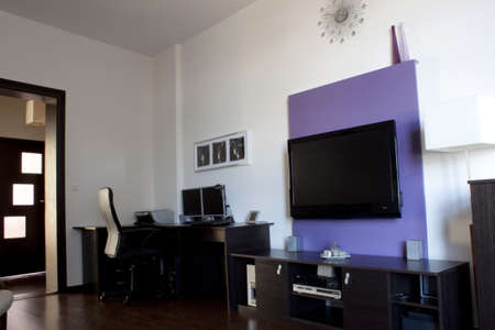Living room with a purple wall of TV  photo