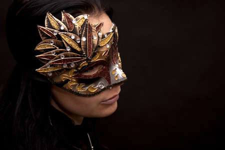 Woman in carnival mask on a black background photo