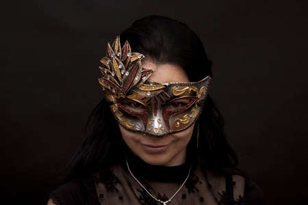 Beautiful woman in mask on a black background photo