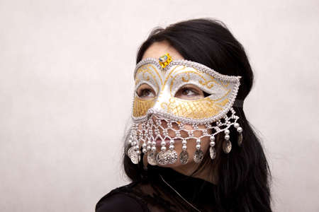 Woman wearing venetian mask on a white background photo
