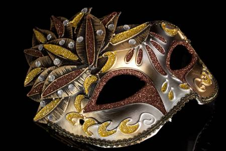 Beige carnival mask with feathers on a black background