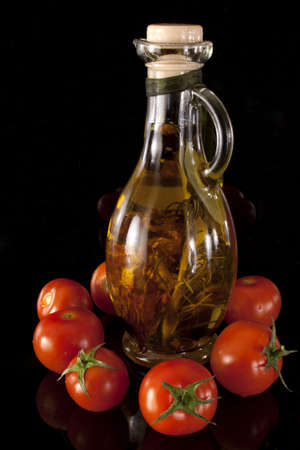 Olive oil and cherry tomatoes on a black background Stock Photo
