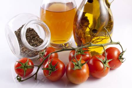 Olive oil, oregano and cherry tomatoes on a white background