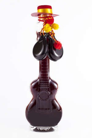 Interesting bottle shaped guitar with red alcohol on white background