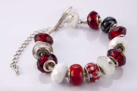 Red and white bracelet with beads on a white background