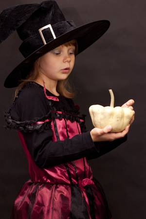 Girl in disguise for Halloween with pumpkin in her hands Stock Photo