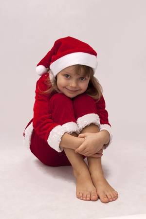 Pretty girl in a red dress Santa Claus sitting on the white background Stock Photo