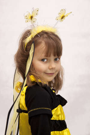 Pretty girl dressed as a bee on white background