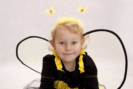 Small girl dressed as a bee on white background
