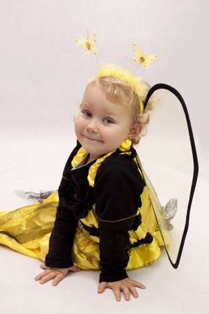 Child dressed as a bee sitting on white background Stock Photo