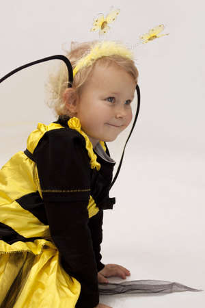 Girl dressed as a bee on white background