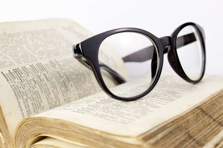 Black glasses and an old dictionary on a white background Stock Photo