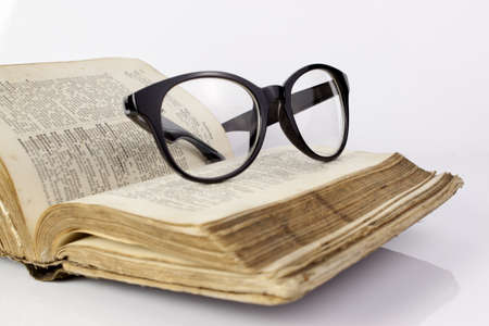 Black glasses on the old dictionary