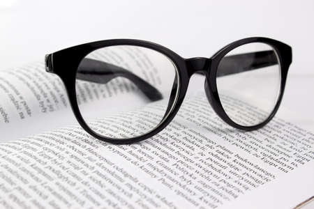 Eyeglasses lying on a book on a white background