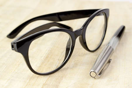 Eyeglasses and pen on old papyrus Stock Photo