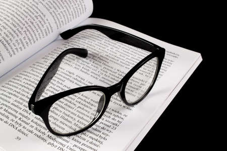 Glasses lying on a book on a black background