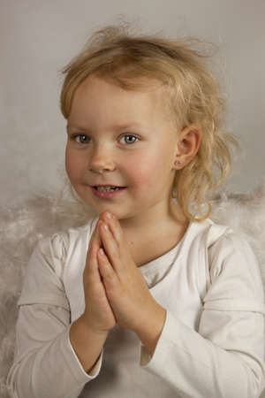 Smiling girl with hands clasped in prayer photo