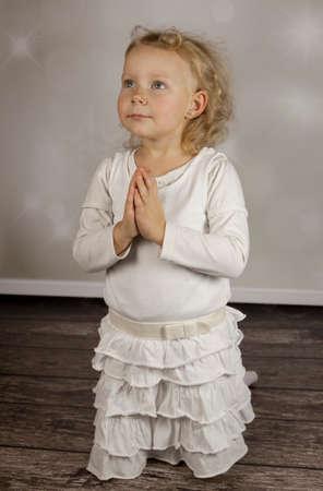 Pretty praying girl in white dress