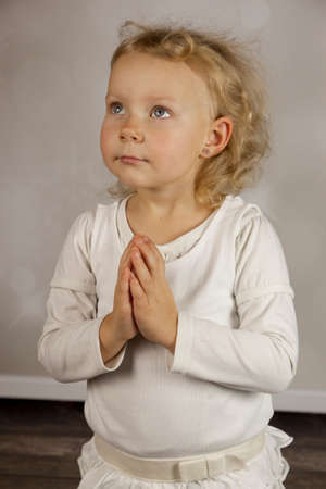 Praying girl in white dress photo
