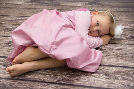 Girl in pink dress lying on the floor Stock Photo