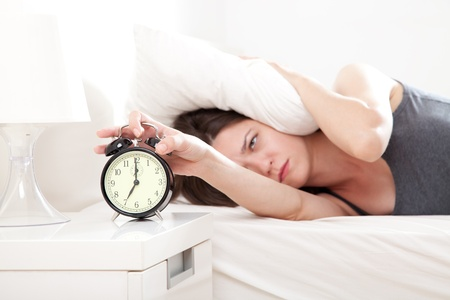 Young woman getting stressed about waking up too early, shallow depth of field, focus on foreground