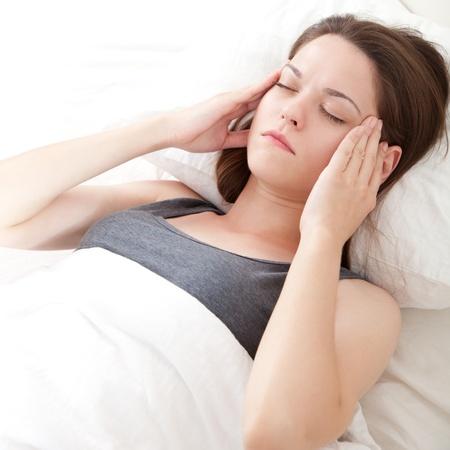 Mooie jonge vrouw, liggend in bed en met migraine Stockfoto
