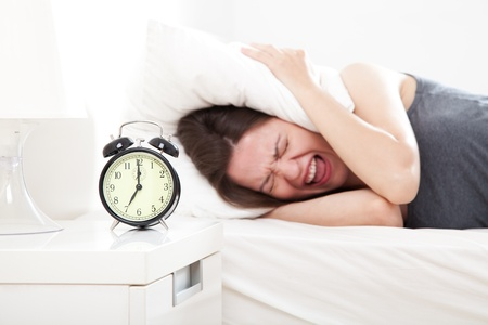 Young woman extremely annoyed by the alarm clock, shallow depth of field, focus on foreground.