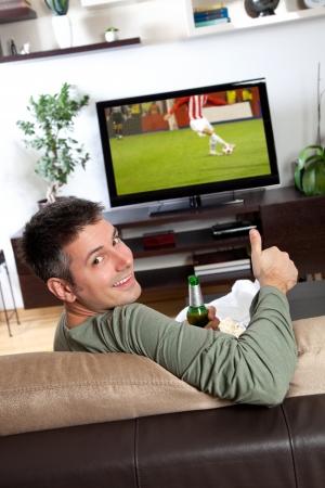 젊은 남자가 편안한 집에서 TV를보고 즐기는 스톡 콘텐츠