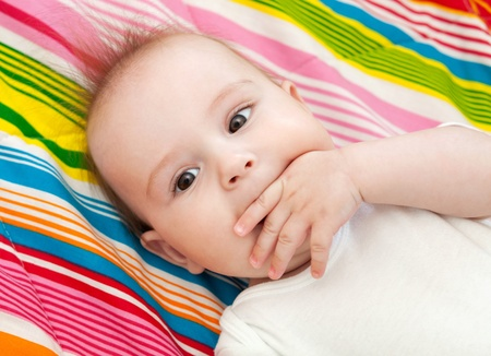 Portrait of a beautiful 6 months baby lying on bed and sucking thumb