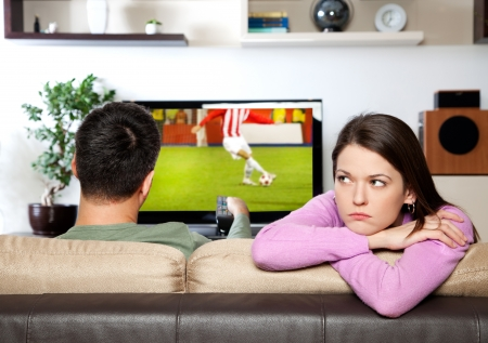 Image of woman getting bored, while her partner watching sportsI am the author of image on TV screen Archivio Fotografico