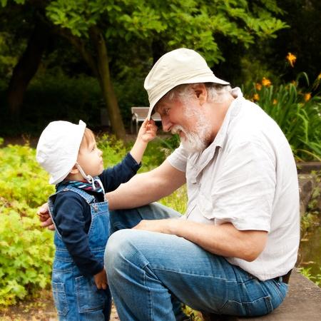 Kleinkind en grootvader plezier buitenshuis.