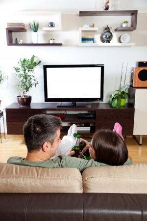 若いカップルのリラックス、テレビを見て、ビールを持って