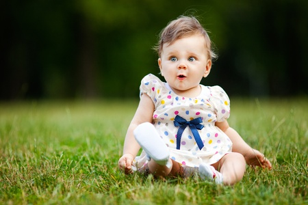 Image of adorable baby girl sitting on grass making funny face, shallow depth of field