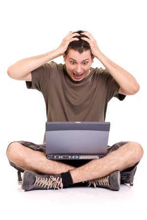 Frustrated young man, holding his head and screaming, sitting with a laptop on white background