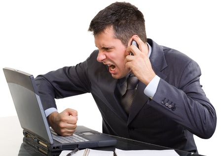 Young caucasian man in a suite, with a phone and laptop screaming and shouting , isolated on white