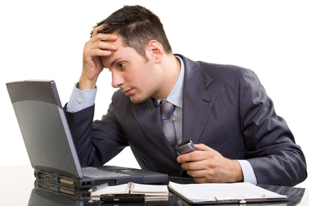 Young Caucasian worried businessman, with a laptop and cell phone