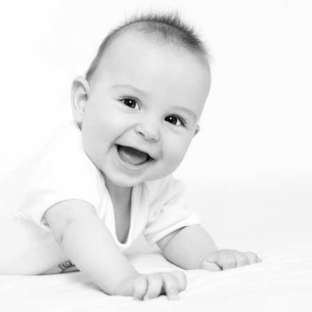 Black and white portrait of a beautiful 6 months baby smiling, on white background