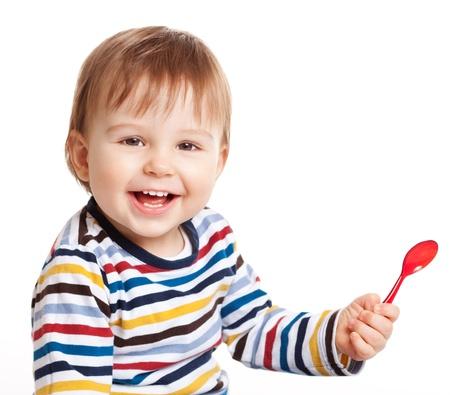 사랑스러운 한 살 아이가 숟가락을 들고 흰색에 격리 미소