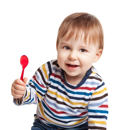 Adorable one year old child holding spoon and smiling, isolated on white