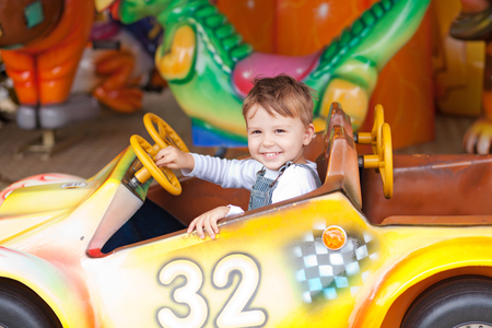 Beautiful boy having fun on the ride at the local carnival 免版税图像
