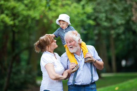 Little boy having fun with his grandparents in park