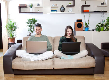 Happy young couple smiling and using laptops 免版税图像 - 30342354