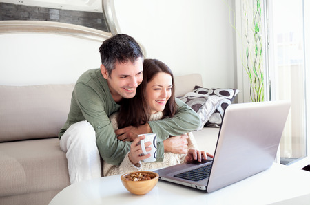 Beautiful young couple relaxing in a living room and using laptop Imagens