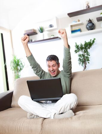 Excited young man with his laptop 免版税图像
