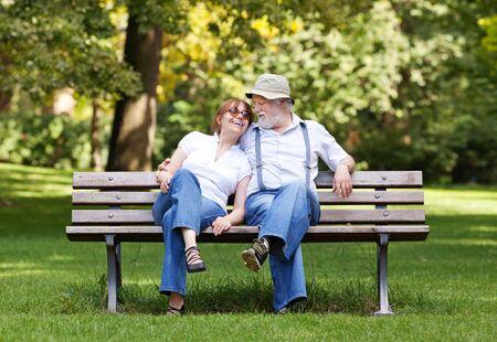 Senior paar zittend op een bankje in het park omhelsde, ondiepe scherptediepte